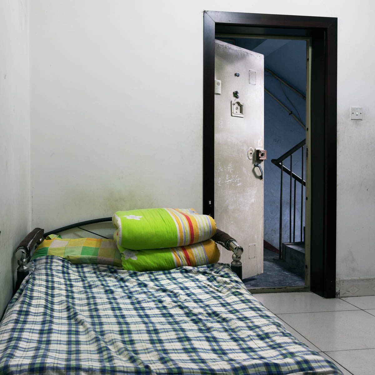"""Lu Chao's and Chen Yi's interior - One bed for two. Chao and Yi sleep in the entrance hall of the apartment belonging to the owner of the Lucky Hair Salon. The place is huge but every room is rented out.  Overwhelmed with work, they only had a few minutes to show us the place.  Chengdu, Sichuan Province, China, April 2012. - Copyright © © S. Borcard - N. Metraux - Chengdu - Sichuan Province - China - <A href=""""https://maps.google.com/?ll=30.662428,104.066055&z=16"""" target=""""_blank"""">(Map Lu Chao's and Chen Yi's interior)</A>"""