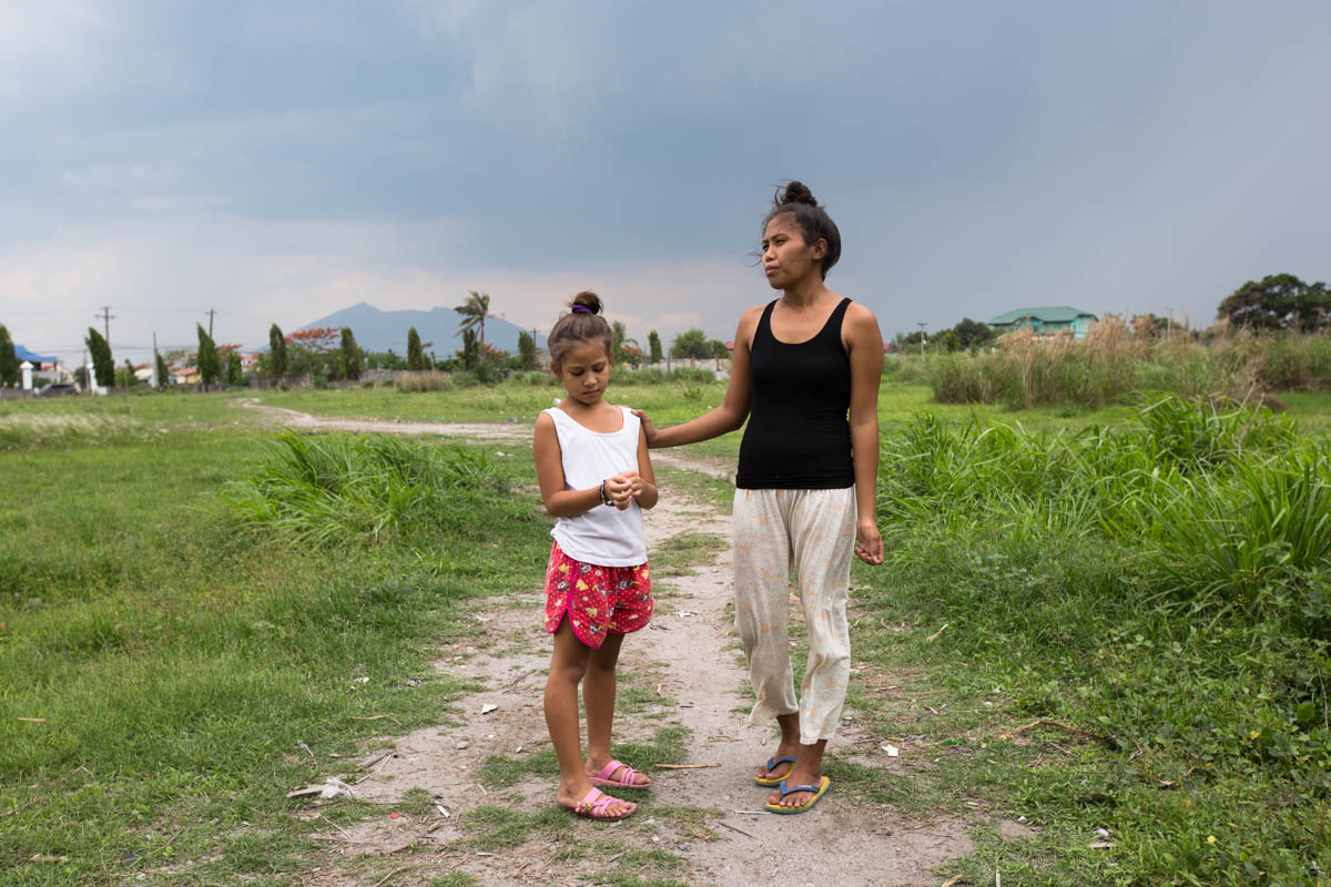 "Nathalie and Blessimai - Nathalie, 32, and Blessimai, 9, on the field behind their house in Mabalacat, 15 km from Balibago. In a few months the construction of a shopping centre will begin here. In the background lies Mount Arayat (1026m), an extinct volcano. Mabalacat near Angeles City, Philippines, May 2015. - Copyright © © S. Borcard - N. Metraux - Mabalacat City - Central Luzon - Philippines - <A href=""https://maps.google.com/?ll=15.228963,120.605763&z=16"" target=""_blank"">(Map Nathalie and Blessimai)</A>"