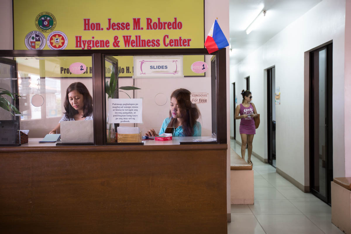 "Hygiene Center - Teresa Lyn, 24, and Charmaine, 38, at the front desk of the Balibago Social Hygiene Clinic. All women working in Fields must be checked for STI's once a week. The result will then be printed on an ID tag that all women must wear while working. The clinic opened its doors in July 2011.  Angeles City, Philippines, May 2015. - Copyright © © S. Borcard - N. Metraux - Angeles - Central Luzon - Philippines - <A href=""https://maps.google.com/?ll=15.166258,120.590958&z=16"" target=""_blank"">(Map Hygiene Center)</A>"