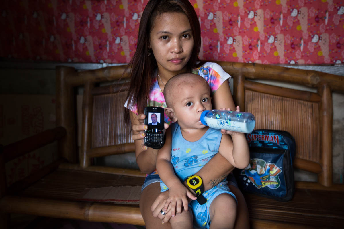 "Joylyn and Renzo - Joylyn, 21 and Renzo, 1, in their home showing the only photo of Renzo's, father, an Australian citizen on a cell phone. Joylyn and Renzo, get no support from him and have lost his contact.  Angeles City, Philippines, June 2015. - Copyright © © S. Borcard - N. Metraux - Angeles - Central Luzon - Philippines - <A href=""https://maps.google.com/?ll=15.17343,120.601083&z=16"" target=""_blank"">(Map Joylyn and Renzo)</A>"