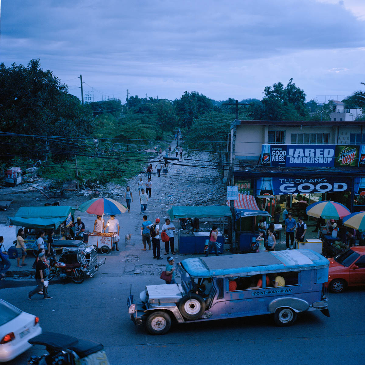 """Balibago at dusk - View from Balibago at dusk. The jeepneys are modified US army jeeps from World War II and transformed into long shared taxis. Jeepneys are the most popular means of public transportation in the Philippines. Angeles City, Philippines, August 2014. - Copyright © © S. Borcard - N. Metraux - Angeles - Central Luzon - Philippines - <A href=""""https://maps.google.com/?ll=15.168055,120.586388&z=16"""" target=""""_blank"""">(Map Balibago at dusk)</A>"""
