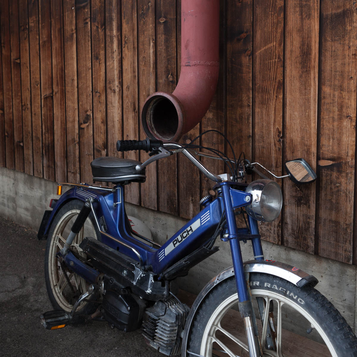 "Puch Motorized Bike - A Puch, a motorized bicycle parked against a wodden wall. A gullter remids of an alphorn. Plaffeien, June, 2012. - Copyright © © S. Borcard - N. Metraux - Planfayon / Plaffeien - Fribourg - Switzerland - <A href=""https://maps.google.com/?ll=46.741653,7.287395&z=16"" target=""_blank"">(Map Puch Motorized Bike)</A>"