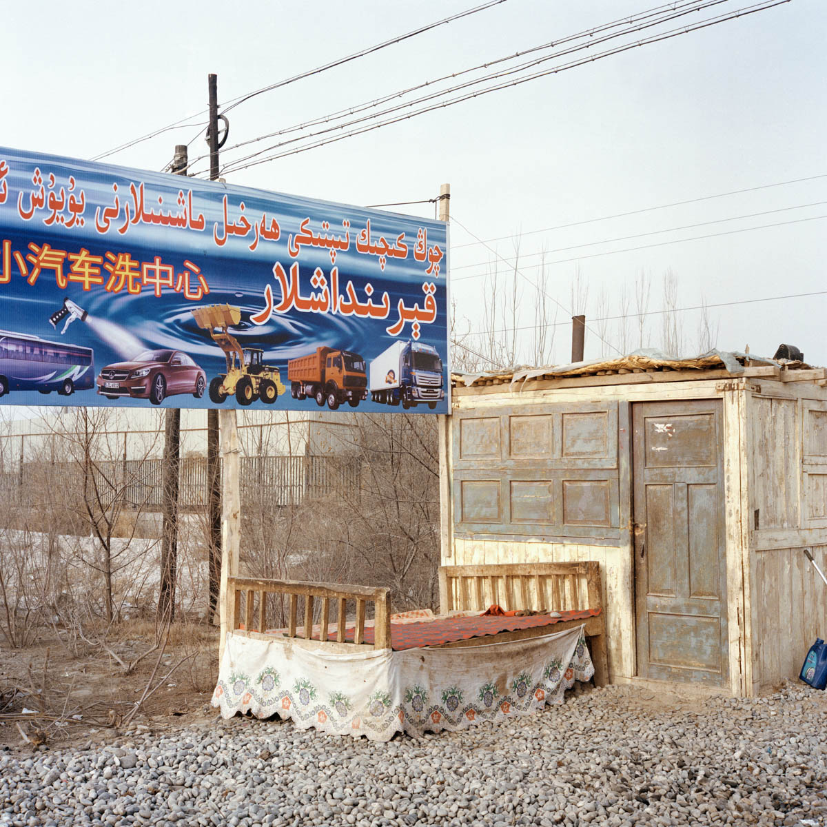 Roadside hut - Roadside hut and advertisement board for caterpillars trucks and cars. A flagrant contrast beween, the ancient times and the modern ones. Hotan, Xinjiang, China 2012. - Copyright © © S. Borcard - N. Metraux -