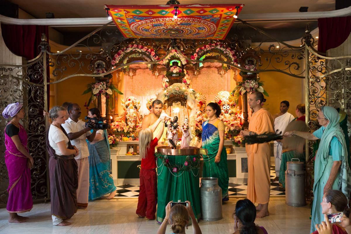 Im Zürcher Tempel der Hare Krishna-Bewegung werden gerade die Murtis, die Statuen von Krishna und seiner Gefährtin Radha, während eines Rituals übergossen. Daneben steht in der gelben Mönchstracht der Vorsteher des Tempels, Krishna Premarupa. ISKCON Tempel, Zürich, August 2017