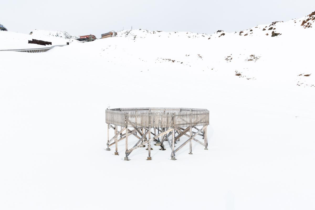 Die Holzstruktur bricht den Wind und hilft den Forschern, die genaue Menge von Schneeniederschlag zu messen. Im Hintergrund steht die Endstation der Parsennbahn. Versuchsfeld Weissfluhjoch, Davos, November 2017.