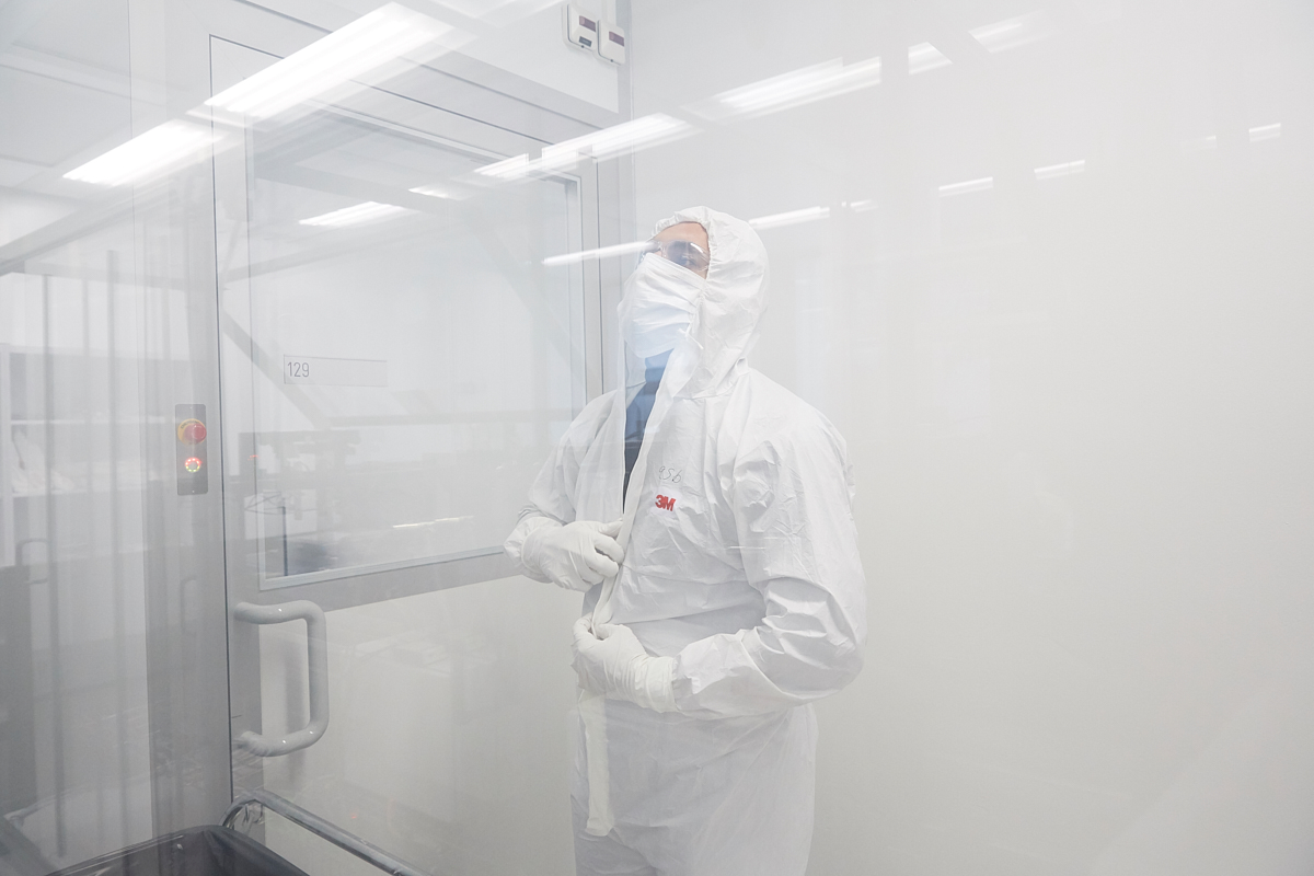 Sina Abdolhosseinzadeh, 32, from Teheran dressing up a white smock gloves, face mask and goggles. The clean room where the enormous printer is, must stay absolutely dust free in order to achieve a maximum printing precision. EMPA, Dübendorf, October 2018.