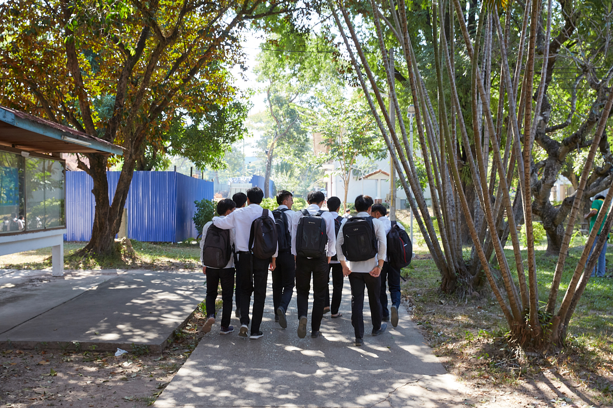Students walking in the shade of trees at the University of Laos engineering campus. Vientiane, Laos, November 2018.