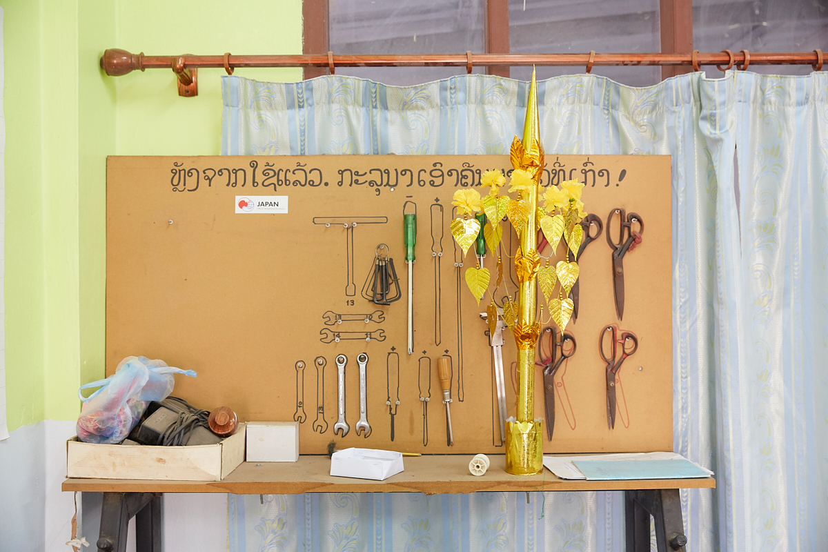 Each tool at its designed place. Japan's Official Development Assistance sponsored sewing machines and tools at the Vientiane Capital Skill Development Center. The golden tree is a typical offering for the Buddha in Laos. It symbolizes the Bodhi Tree under which Siddhartha Gautama is said to have attained enlightenment. Vientiane, Laos, November 2018.