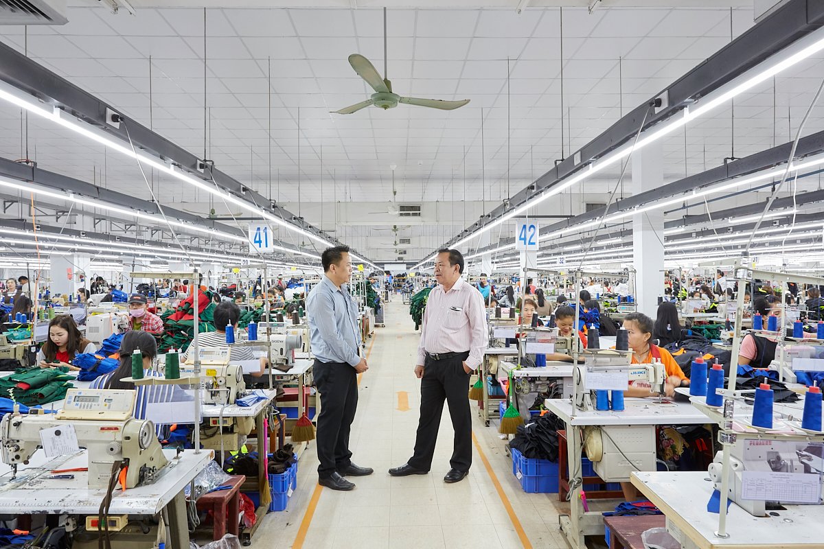 Mr. Santiphap talking with the CEO of the TRIO (Lao) Export Co. Ltd, Lao's biggest garment factory where over 2500 employees work. The average income of a worker is about 250 USD a month. In Laos, as in most other developing countries, the garment industry workers are mostly female. Vientiane, Laos, November 2018.